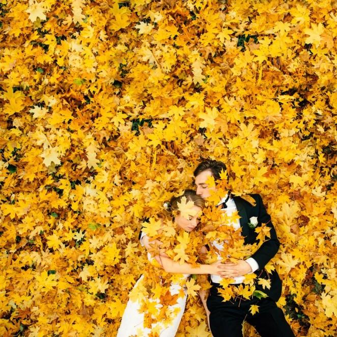 Жених и невеста лежат на осенних листьях