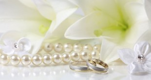 Кольца на свадьбу на зеркальной поверхности в окружении лилий