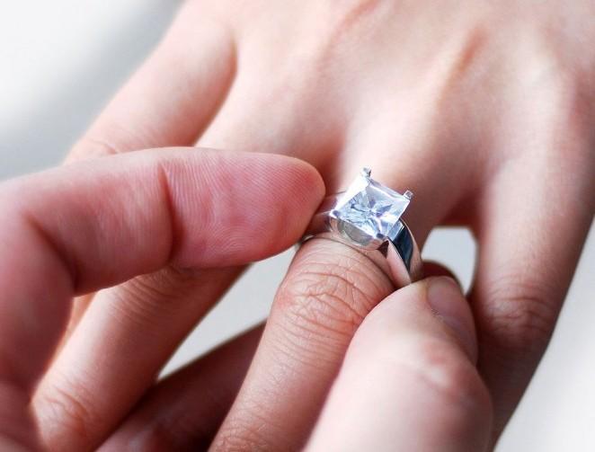 парень надевает девушке кольцо на руку